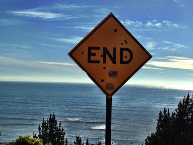 sign that says end in front of ocean and sky
