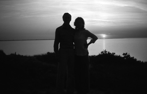 black and white silhouette of man and woman at sunset by the ocean