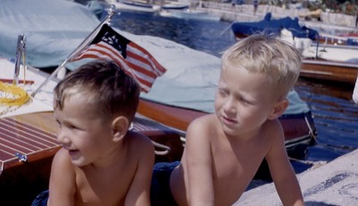 two young boys in bathing suits looking left at the harbor